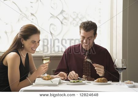 Mid adult Caucasian couple dining in restaurant and laughing.