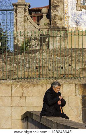 PORTO, NORTE, PORTUGAL - DECEMBER 6, 2015: Woman in front of Church of Saint Ildefonso in Porto in Portugal