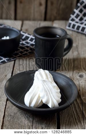 Meringues and cup of tea on a gray wooden table