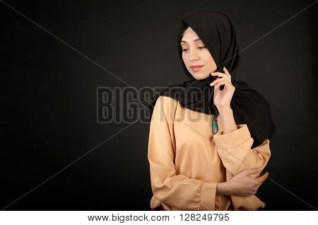 photo of a young oriental woman in modern clothes with a Muslim in a scarf on a dark background