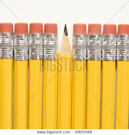 Even row of eraser ends of pencils except for one that has the pointed end up.