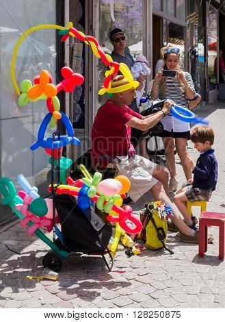 Tel Aviv, Israel, 28 April 2016: street vendor of inflatable balls makes for a boy a crown of ball in Tel Aviv, Israel