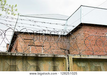 Barbed wire on a fence on a background of a brick building