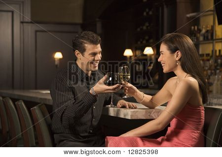 Mid adult Caucasian couple at bar toasting wine glasses and smiling.