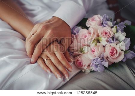bride and groom's arms with rings and a wedding bouquet