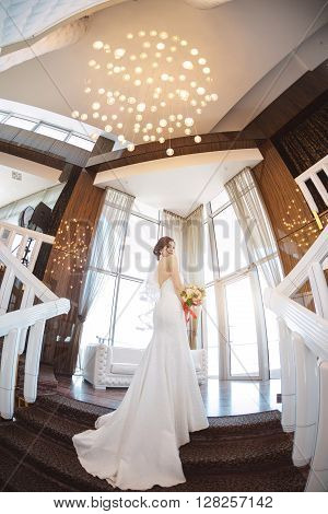Beautiful bride in white wedding dress standing on stairs near the window. Fisheye lens