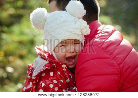 photo of little crying sad girl with funny hat