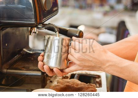 Barista mixing milk on espresso machine for making coffee Latte and cappuccino at the coffee machine at the coffee shop