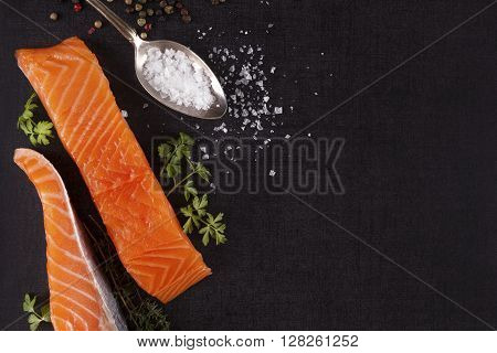 Salmon background with copyspace. Salmon steak lemon rosemary and parsley leaf and salt on black background flat lay.