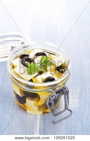 Marinated greek feta cheese in glass jar on blue wooden background. Culinary marinated cheese rustic styles.