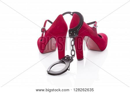 Red high heels and handcuffs isolated on white background. Sexy seductive and submissive.