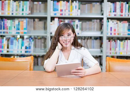 young beautiful asian girl with tablet in school library