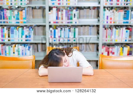 young beautiful asian girl with laptop in school library