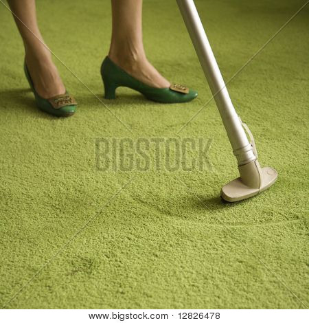 Close-up of Caucasian female feet with vacuum extension against green retro carpet.