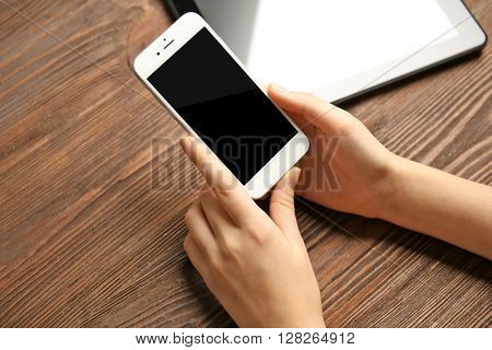 A tablet and female hands using mobile phone, on the wooden background