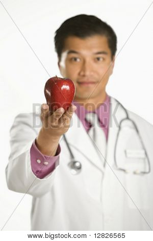 Asian American male doctor holding out apple.