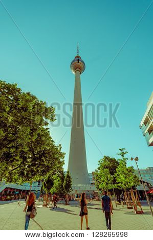 BERLIN, GERMANY - JUNE 06, 2015: One of most important buildings in Berlin, Fernsehturm in the center of the city. people walking around,