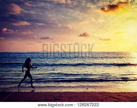 Healthy sporty fitness fit life concept - vintage retro effect filtered hipster style image of  beautiful athletic woman running along sea on the beach in the morning