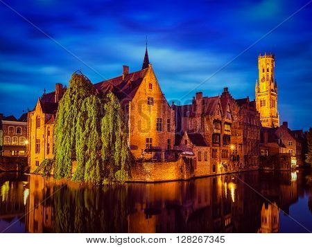 Famous view of Bruges-  vintage retro effect filtered hipster style image of Belfry and old houses along canal with tree. Brugge, Belgium