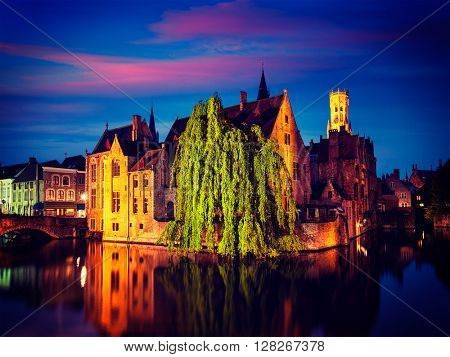 Famous view of Bruges - vintage retro effect filtered hipster style image of Rozenhoedkaai with Belfry and old houses along canal with tree in the night. Brugge, Belgium