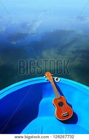 Ukulele lay on blue boat floating on water relax with instrumental Ukulele