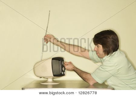 Side view of Caucasian mid-adult man sitting at 50's retro dinette set adjusting old television antenna.