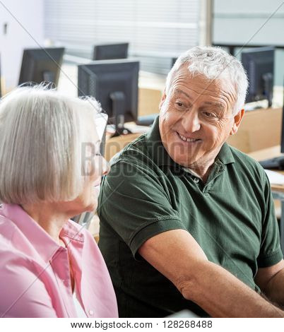 Senior Man Talking To Classmate In Computer Class