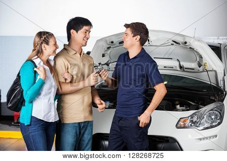 Happy Couple Giving Car Keys To Technician