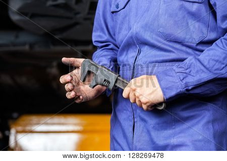 Mechanic Holding Adjustable Wrench In Garage