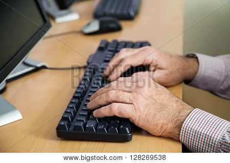 Senior Man Using Keyboard In Computer Class