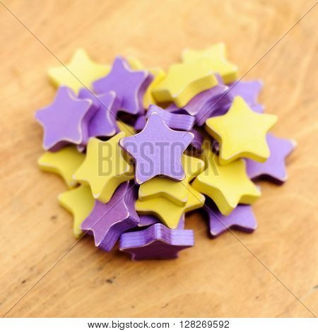 yellow and violet wooden distressed stars on wooden background
