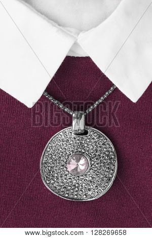 Silver medallion on maroon pullover with white collar closeup