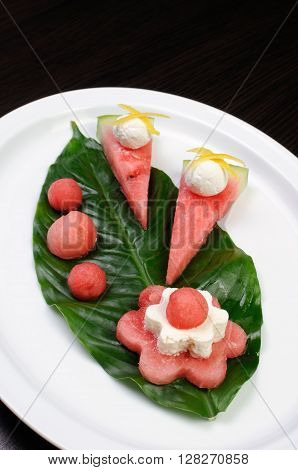 Decorative design of watermelon snack with ricotta on a green leaf
