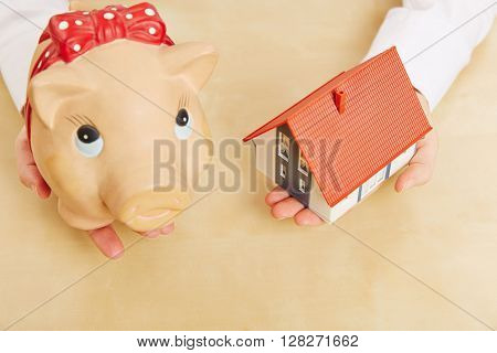 Two hands holding a small house and a piggy bank as real estate mortgage concept