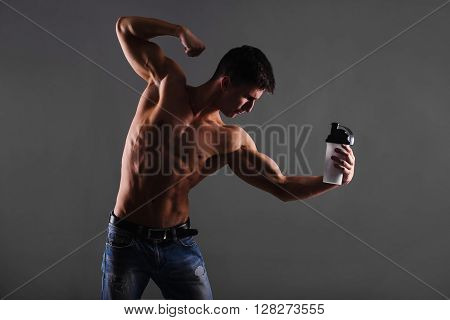 Strong Athletic Man Fitness Model With Shaker Isolated On Gray Background, Men's Physique