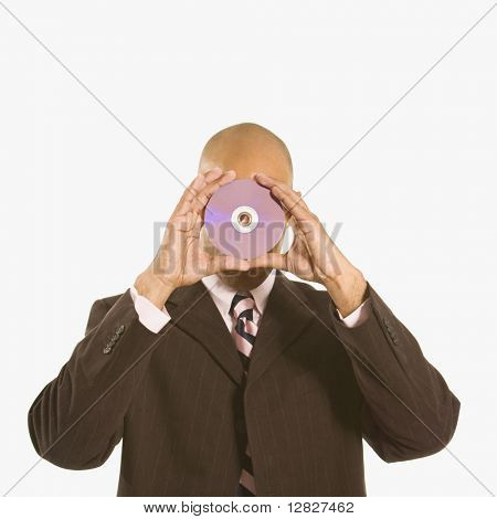 African American man holding compact disc over his face.