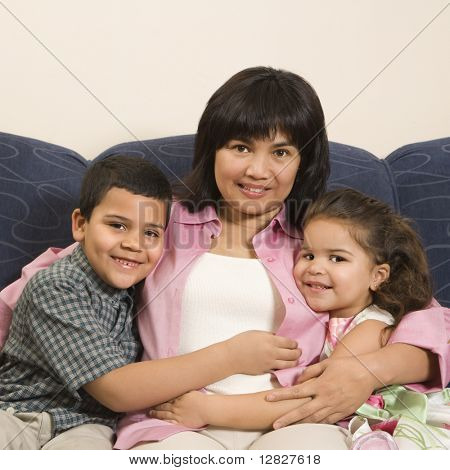 Family sitting on couch hugging each other smiling and looking at viewer.