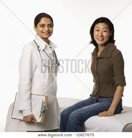 Indian woman doctor with Asian woman patient.
