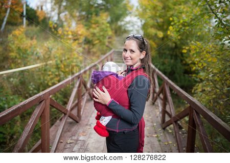 Mother carrying her cute baby daughter in sling, standing on wooden bridge outside in autumn nature