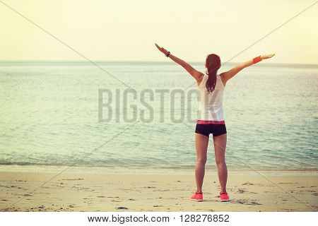 cheering young fitness asian woman open arms on beach