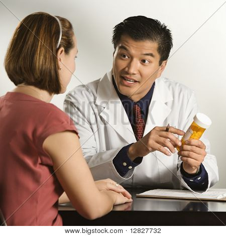 Asian American male doctor explaining medication to Caucasian female patient.