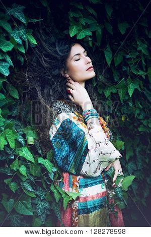 young  pensive long hair woman portrait in ivy wearing long silky dress