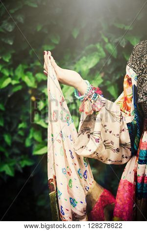 detail of boho style summer dress hold by female hand outdoor shot