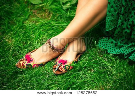 female legs on grass in leather ethnic boho summer sandals