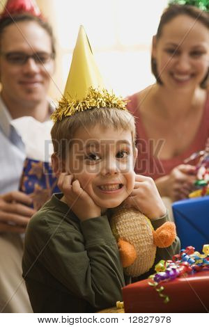 Caucasian boy at  birthday party looking at viewer making facial expression.