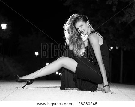 Smart young pretty blonde woman crouching on the floor at night outdoors looking at camera and showing leg, black and white