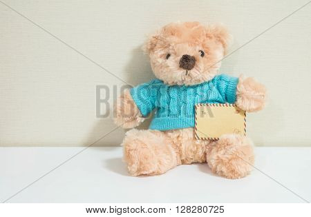 Closeup brown envelope with brown bear doll on wall room background