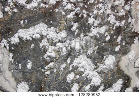 Stone background closeup texture of marble with snow