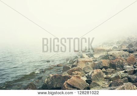 Landscape with fog over lake and stones