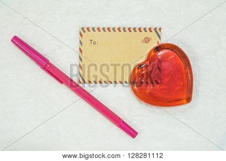 Closeup red glass in heart shape with brown envelope and pink pen on fabric texture background in valentine theme